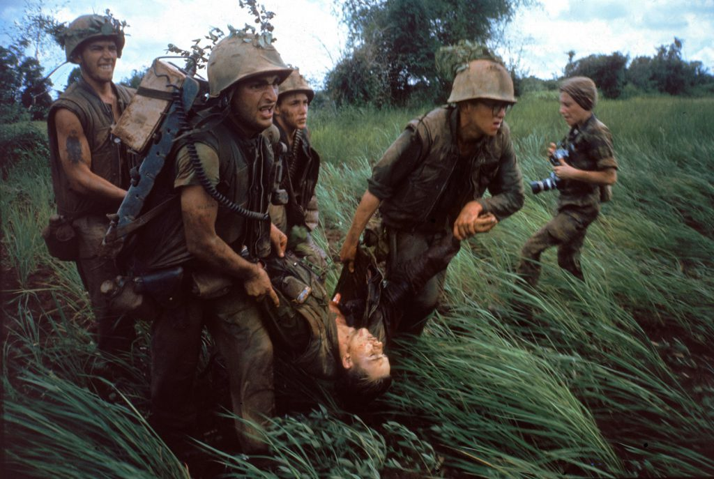 "Caption from LIFE. ""Four Marines recover the body of a fifth as their company comes under fire near Hill 484."" Vietnam, October 1966. NOTE: At right is the French-born photojournalist Catherine Leroy (1945 Ð 2006); she was cropped out of the version of this photo that originally ran in LIFE."