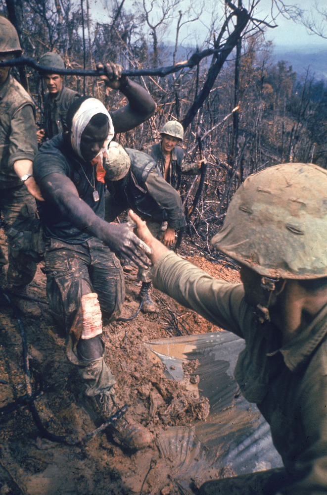 American Marines aid a wounded comrade during Operation Prairie near the DMZ during the Vietnam War, October 1966.
