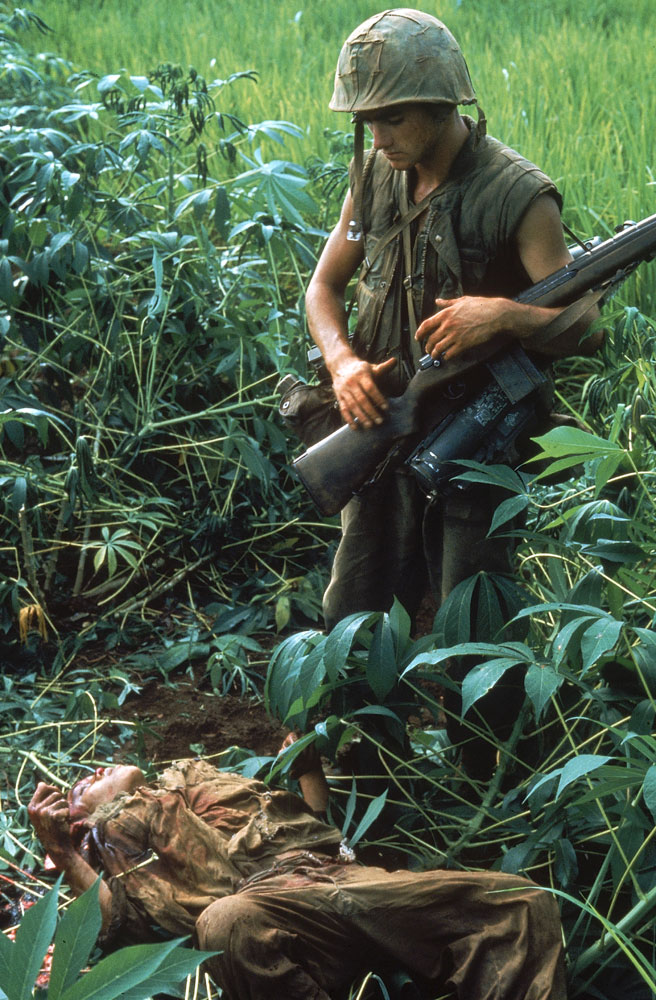 Not published in LIFE. An American Marine looks at the body of a North Vietnamese killed during Operation Prairie near the DMZ during the Vietnam War, October 1966.