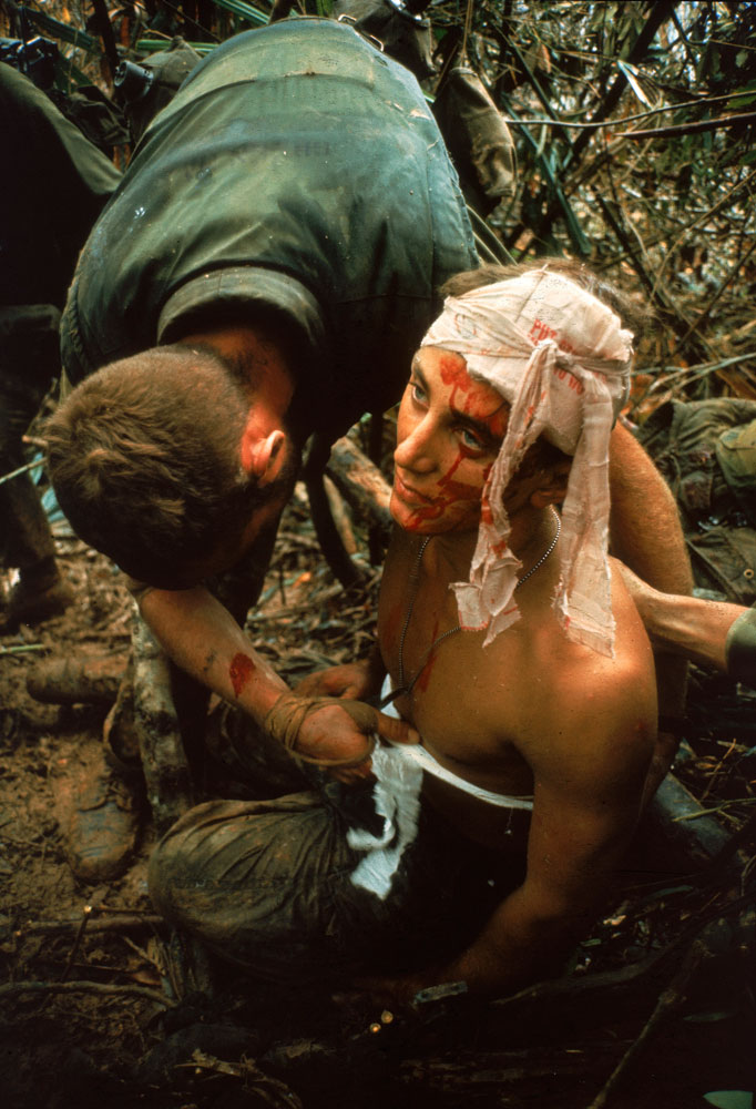 Not published in LIFE. A dazed, wounded American Marine gets bandaged during Operation Prairie near the DMZ during the Vietnam War, October 1966.