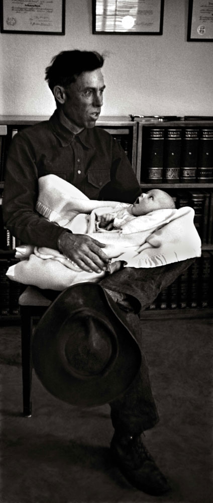 Ralph Pickering holds his 5-week-old baby while waiting to be Dr. Ceriani's first patient of the day. Pickering, a horseback guide to tourists coming to see the majestic Rocky Mountains, traveled from an outlying ranch to reach the doctor's office.