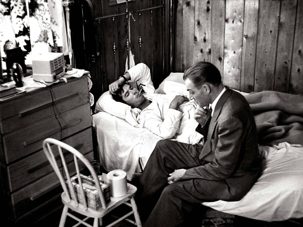 "Dr. Ceriani sits at bedside of a patient as he assesses flu symptoms during a house call. When Smith began ""Country Doctor,"" he shot for a period of time with no film in his camera, to help Ceriani get used to his presence without wasting precious film."