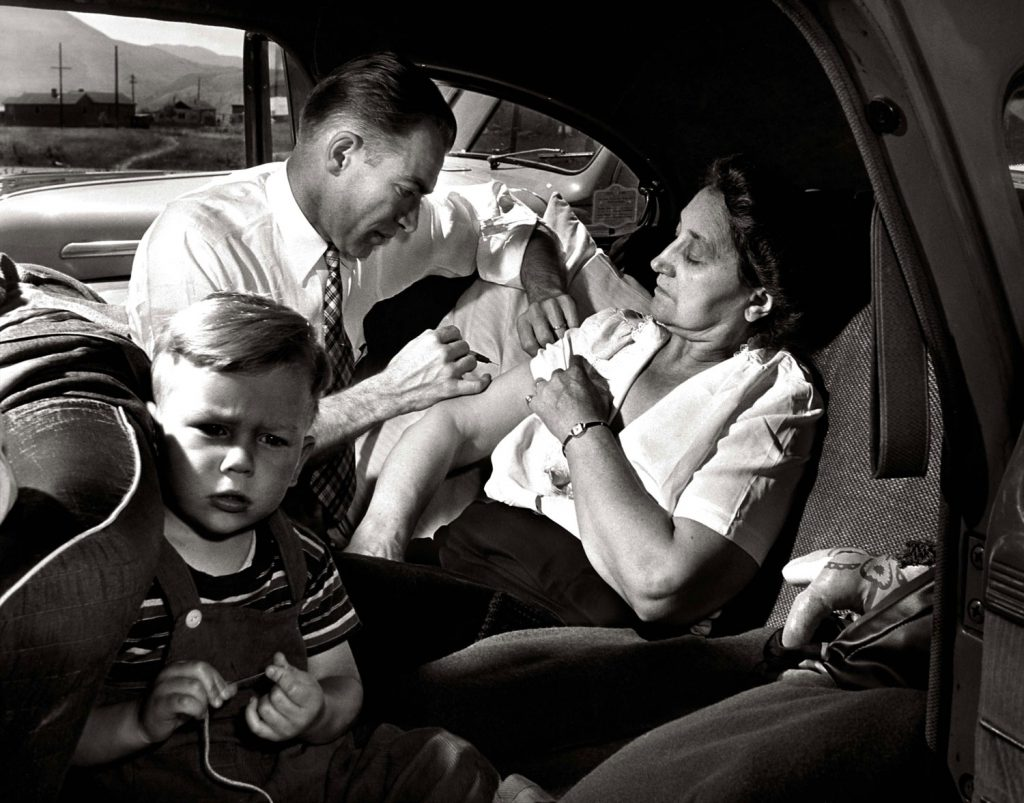 In the backseat of a car, Dr. Ceriani administers a shot of morphine to a 60-year-old tourist from Chicago, seen here with her grandson, who was suffering from a mild heart disturbance.