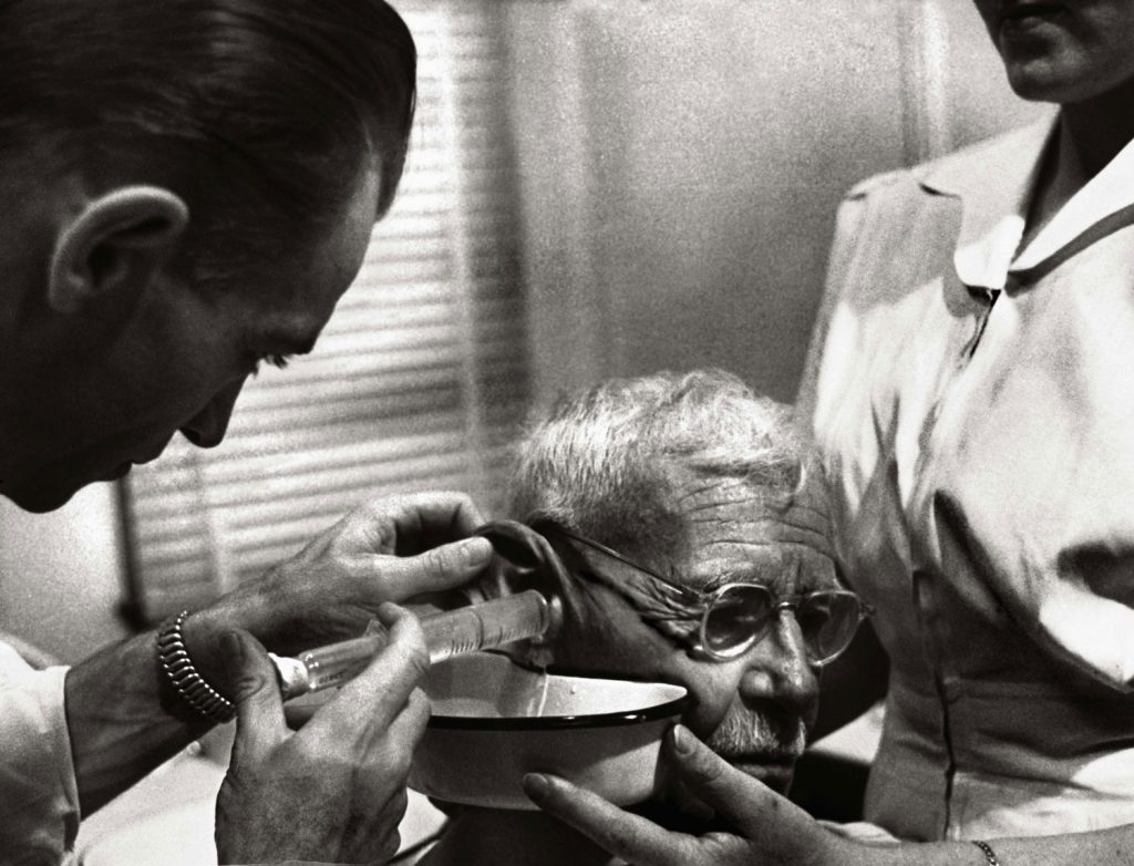Dr. Ceriani uses a syringe to irrigate wax from an elderly man's ear to improve his hearing.