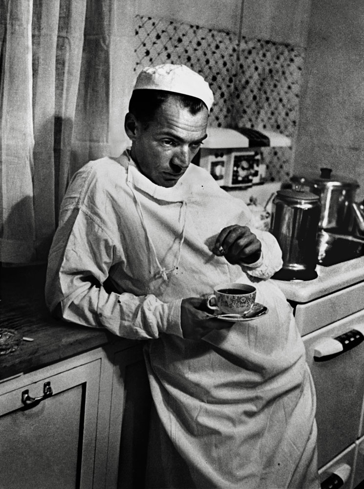 "After finishing a surgery that lasted until 2 AM, Dr. Ceriani stands exhausted in the hospital kitchen with a cup of coffee and a cigarette. ""The nurses,"" LIFE noted, ""constantly admonish him to relax and rest, but because they are well aware that he cannot, they keep a potful of fresh coffee simmering for him at all hours."""