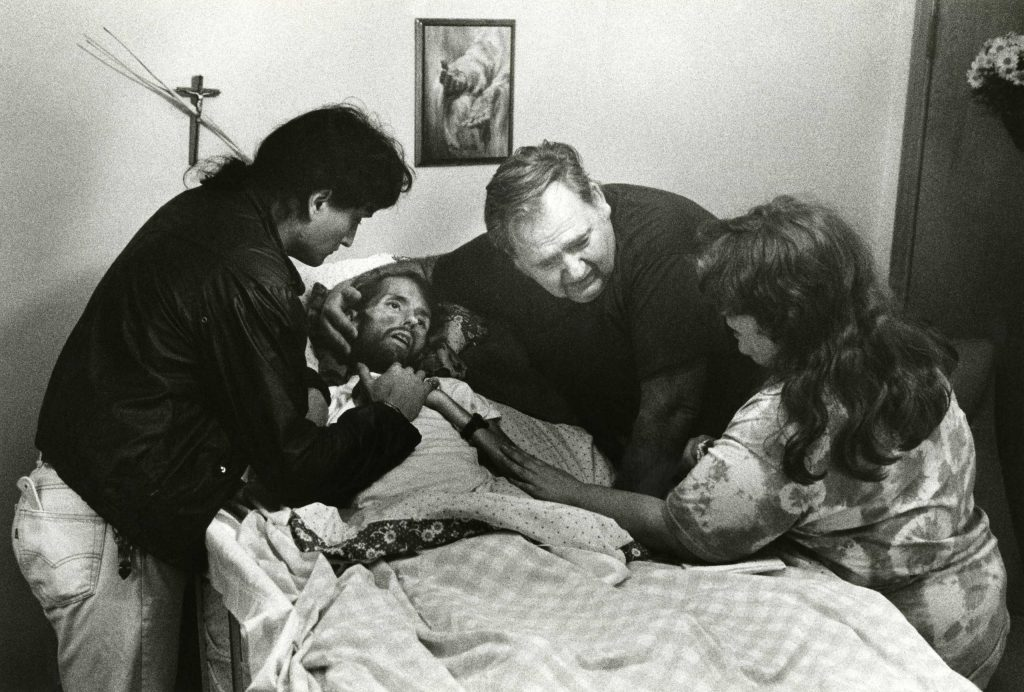 In another of Therese Frare's photos taken in the final moments of David Kirby's life, his caregiver and friend, Peta; David's father; and David's sister, Susan, say goodbye.