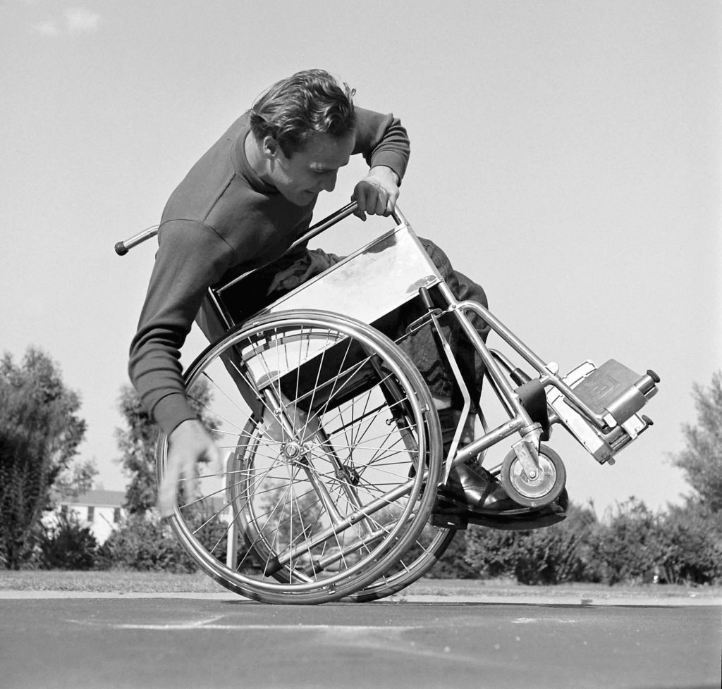 Marlon Brando attempts to tip and balance his wheelchair on the set of The Men, 1949.