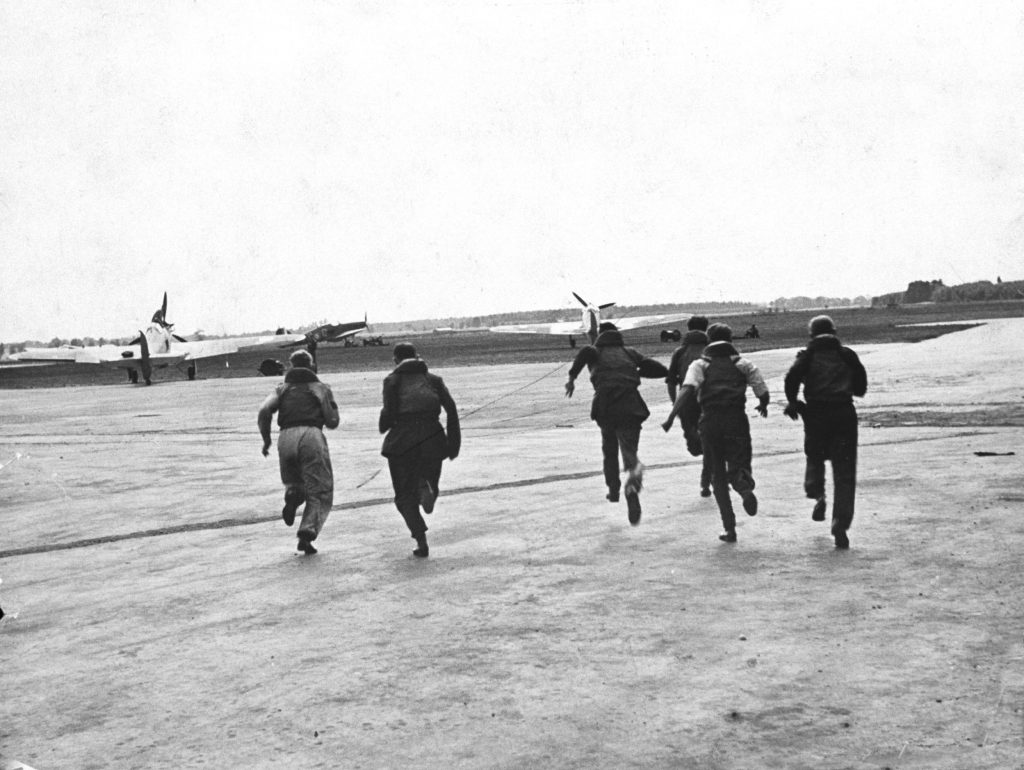Pilots and aircrew members scramble to their planes during the Battle of Britain, RAF Fighter Command airfield, 1940.