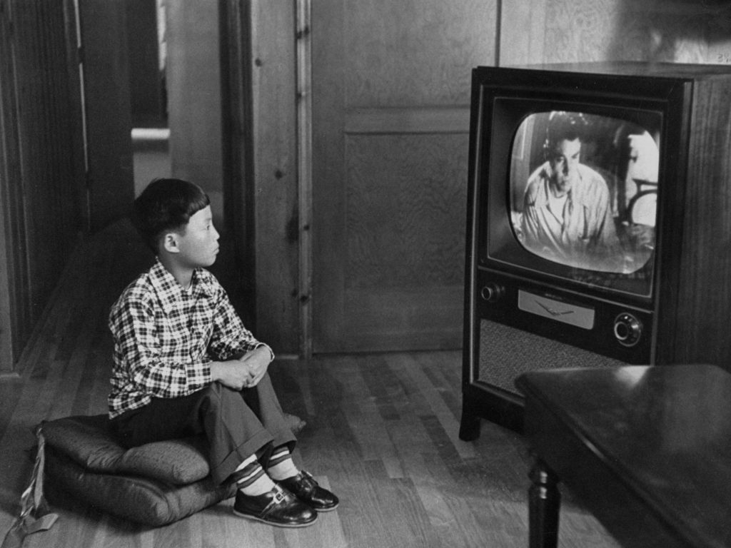 An adopted Korean war orphan, Kang Koo Ri, watches television in his new home in Los Angeles in 1956.
