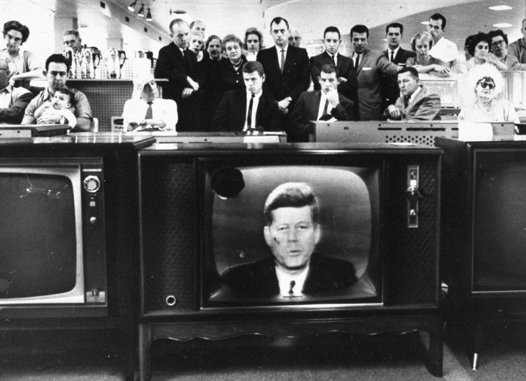 A crowd watches John F. Kennedy address the nation during the Cuban Missile Crisis, October 1962.