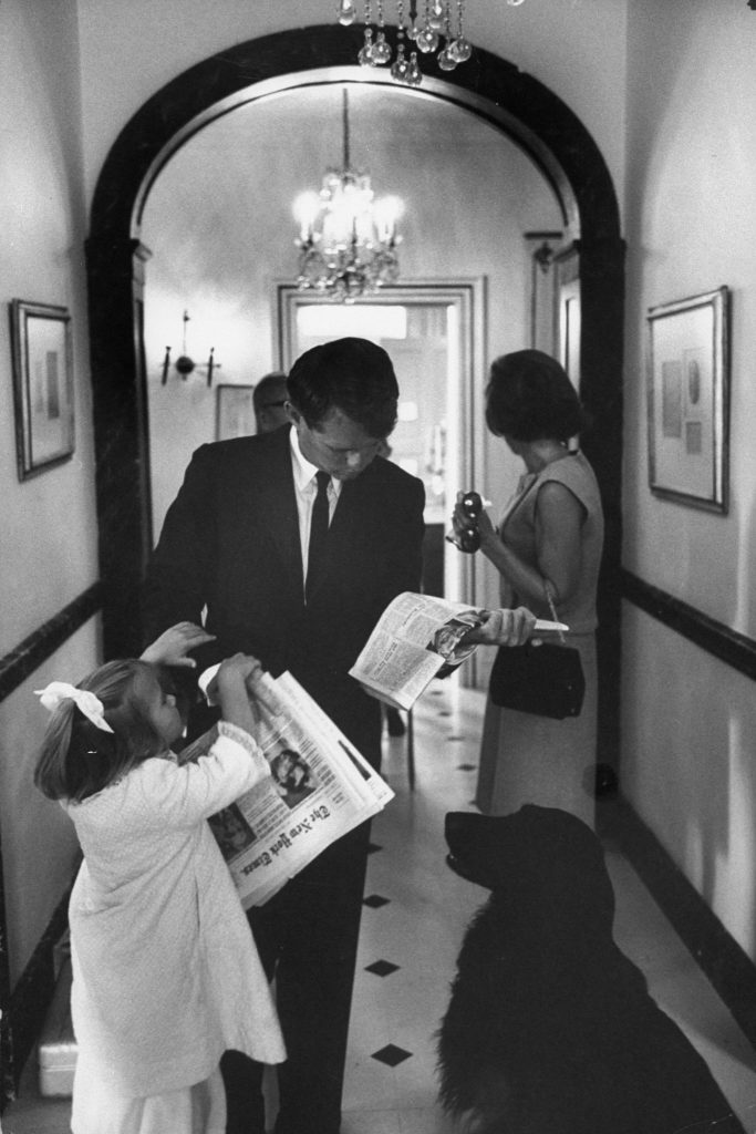 On his way to the office, Kennedy stands in hall at Hickory Hill with wife, Ethel, scanning the headlines while his daughter Kerry, 4, tugs for a goodbye kiss.