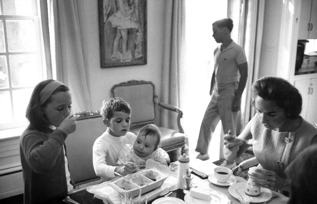 Ethel finishes her meal as Michael, 6, holds Christopher, one, in lap and 7-year-old Courtney tempts baby by testing his food. Joseph, 11, looks out window.