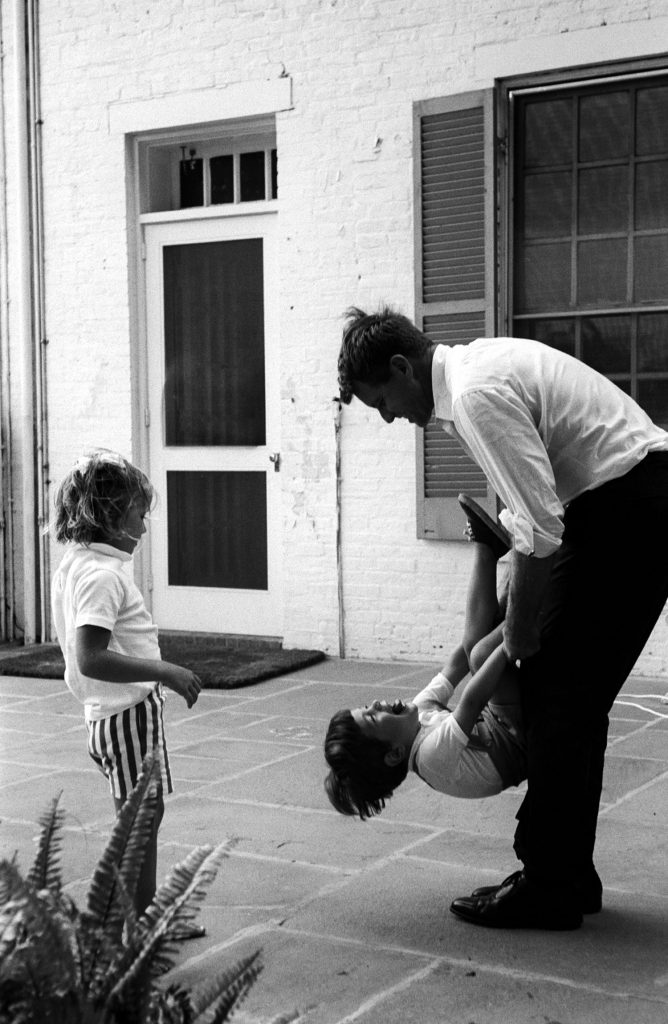 Bob swings his nephew on terrace. 'Jack made John the mischievous, independent boy he is,' says Jackie Kennedy. 'Bobby is keeping that alive.'