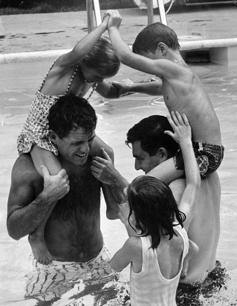 Robert Kennedy and Pierre Salinger joust with kids in Kennedy's pool, 1964.
