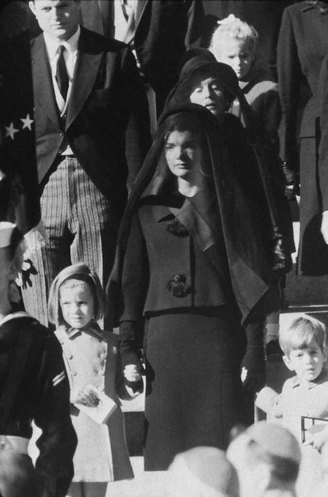 Wife. Mother. Niece. Three generations wait outside St. Matthew's for procession to cemetery. Behind Mrs. Kennedy stands the President's mother. Sydney Lawford, daughter of Kennedy's sister Pat, is at rear.