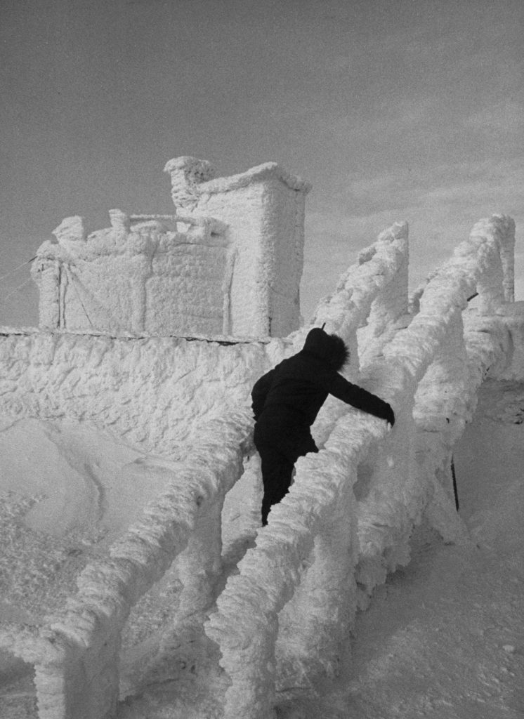 A technician clambers around Summertime Hotel which, in dead of winter, stands castle-like and forbidding, its doors and windows sealed with foot of ice.