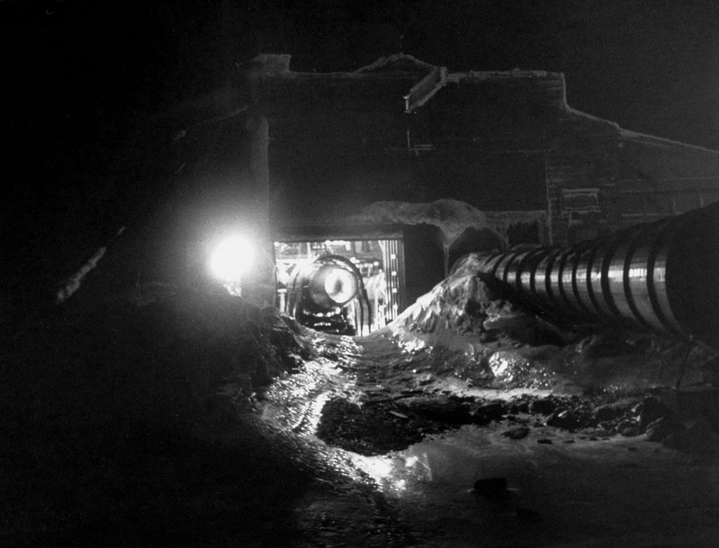 Jet test, carried on in an open-front steel hangar, is run day and night to measure and photograph ice which forms at the intake on the inside of mounted engine. Depression in snowbank is created by the engine's fiery blast. . . . When engine is turned off, water quickly refreezes rock-hard.