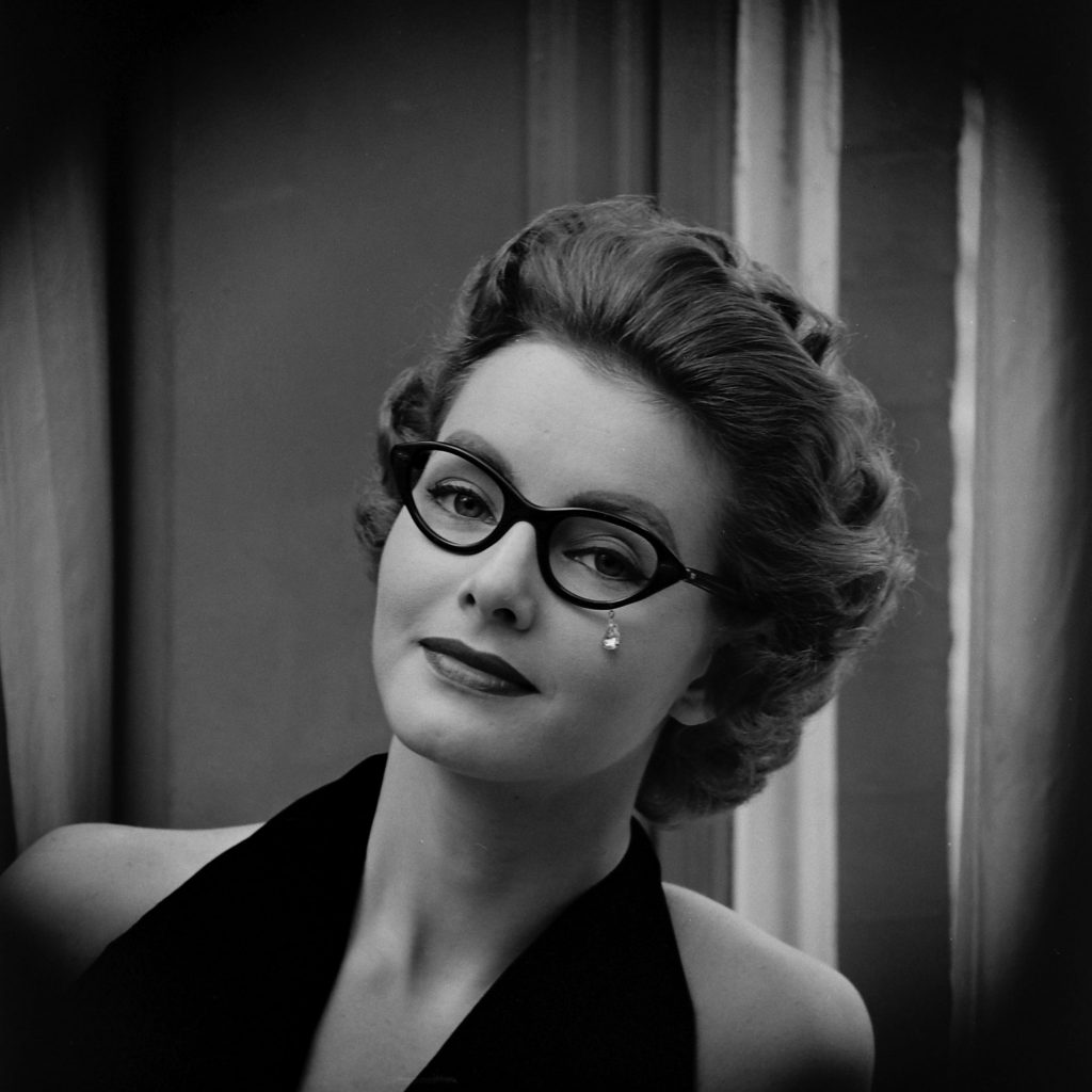 Glasses have no lenses, but feature what looks to be a costume jewelry tear-drop dangling from the frame.
