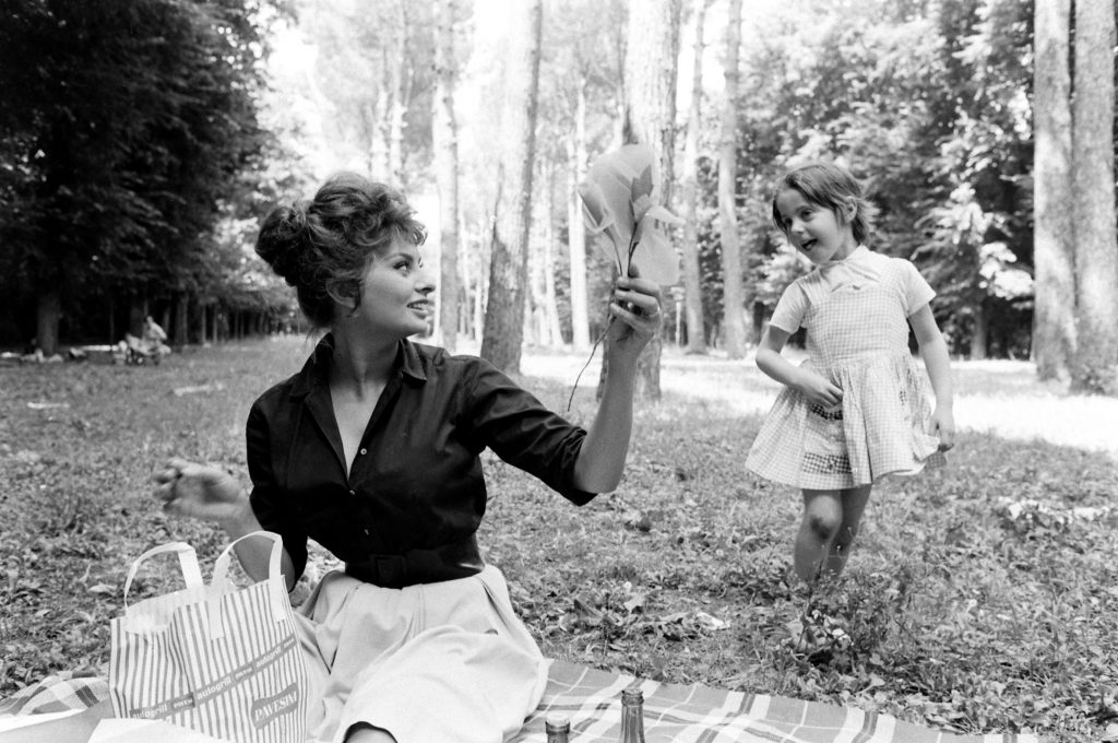 Sophia Loren with an unidentified child, Italy, 1961.