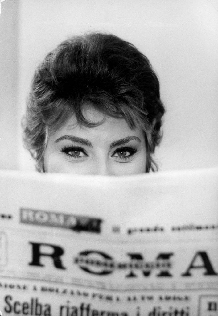Sophia Loren impishly peering over the top of a newspaper.