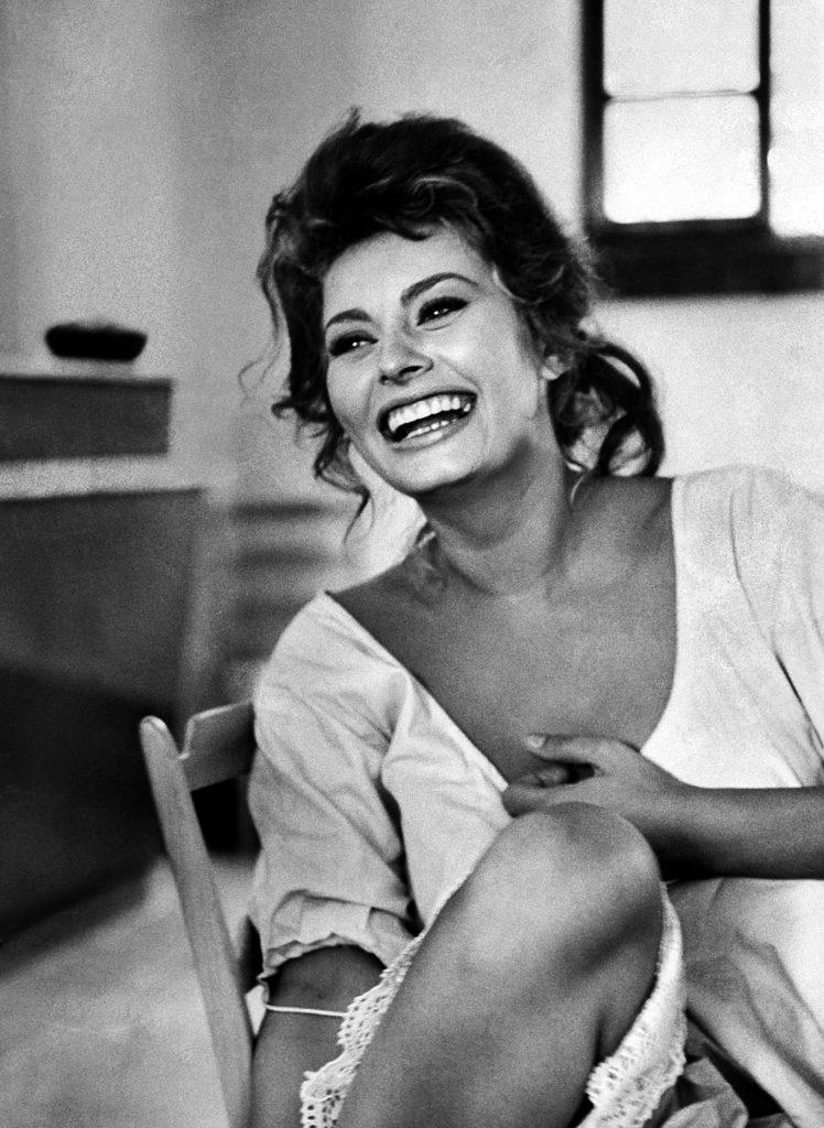 Sophia Loren laughing while exchanging jokes during lunch break on a movie set.