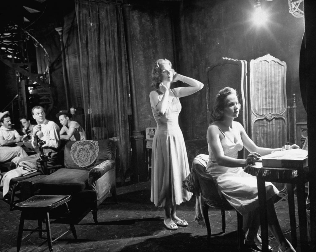 Blanche and Stella (Kim Hunter) undress in a bedroom which is divided from living room by partly closed curtains. Though Blanche complains about the noisy poker party which is going on in the adjoining room, she purposely stands so she can be seen by Mitch (Karl Malden, third from left).