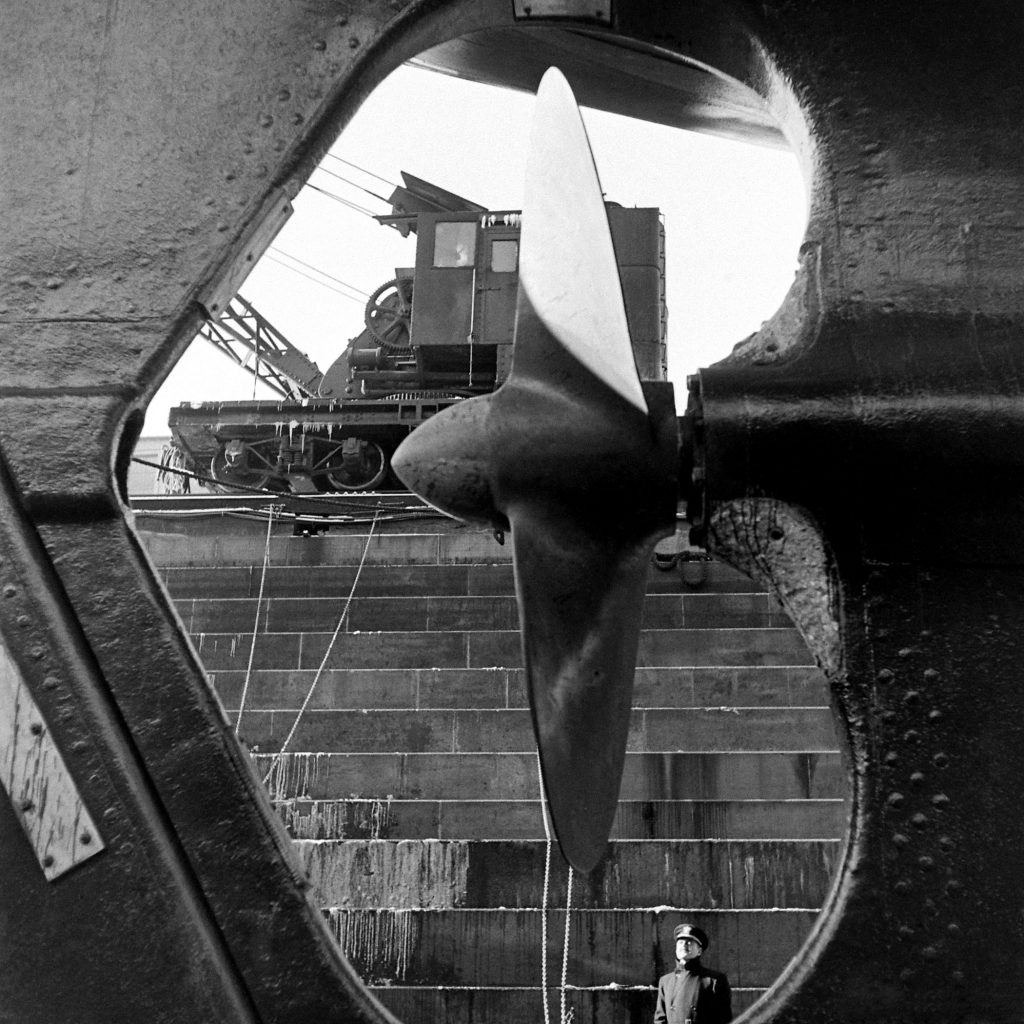 A Naval officer gazes at a cruiser's propeller at the Brooklyn Navy Yard.