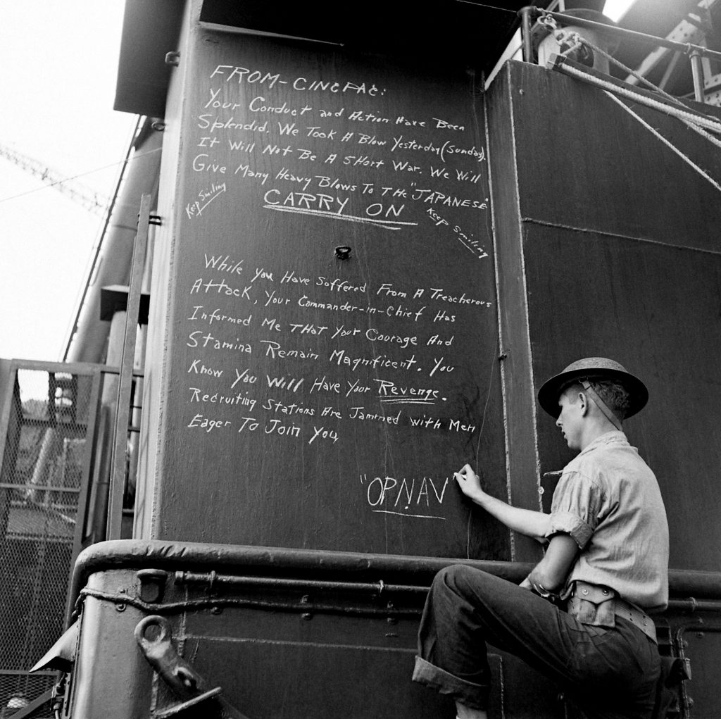 A sailor chalks a message to America's fighting men from the Office of the Chief of Naval Operations on a warship at Pearl Harbor.