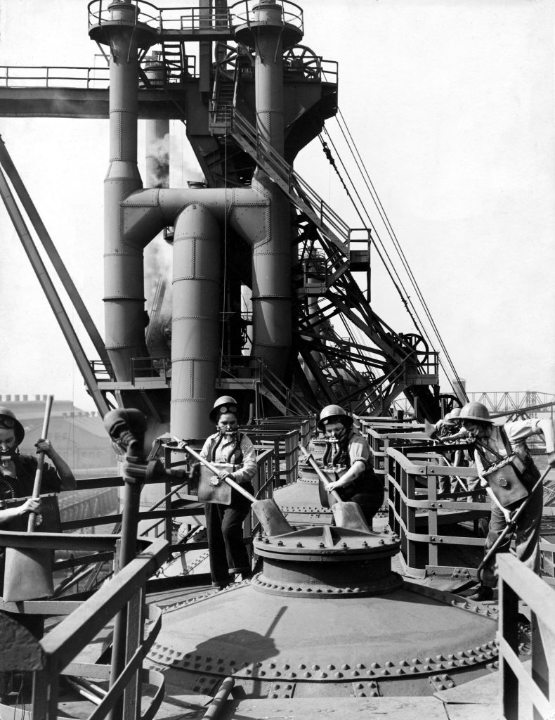 Women wearing gas masks clean a blast furnace top at a Gary, Ind. steel mill, 1943.