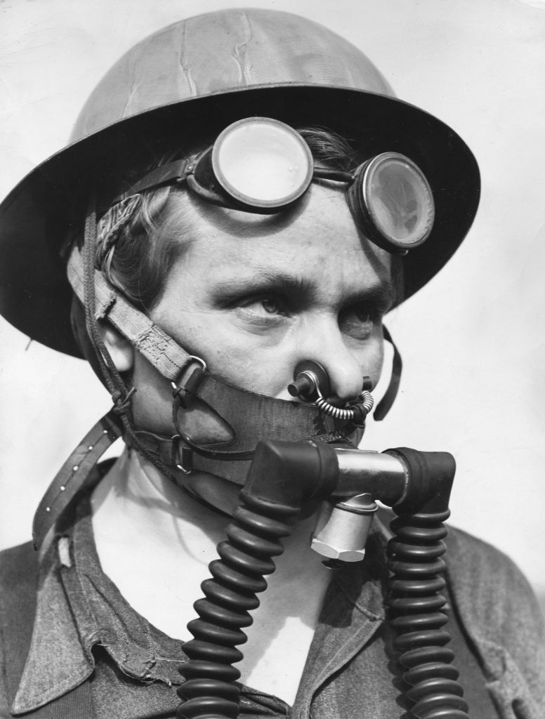 """Bernice Daunora, 31, a member of a steel mill's """"top gang"""" who must wear a """"one-hour, lightweight breathing apparatus"""" as protection against gas escaping from blast furnaces, Gary, Ind., 1943."""