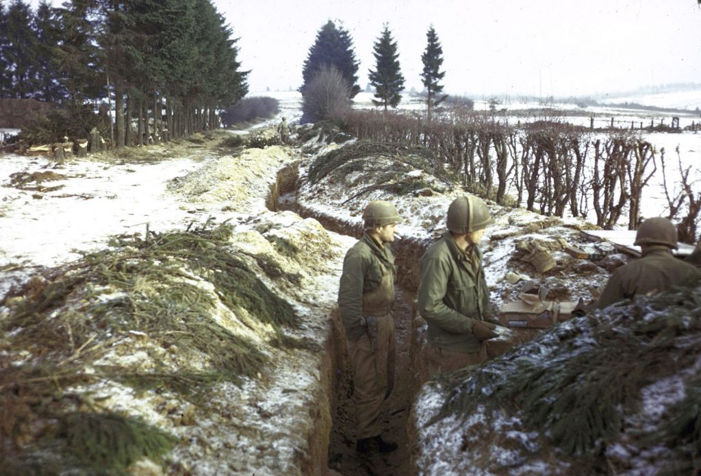 American troops man trenches along a snowy hedgerow in the northern Ardennes Forest during the Battle of the Bulge.