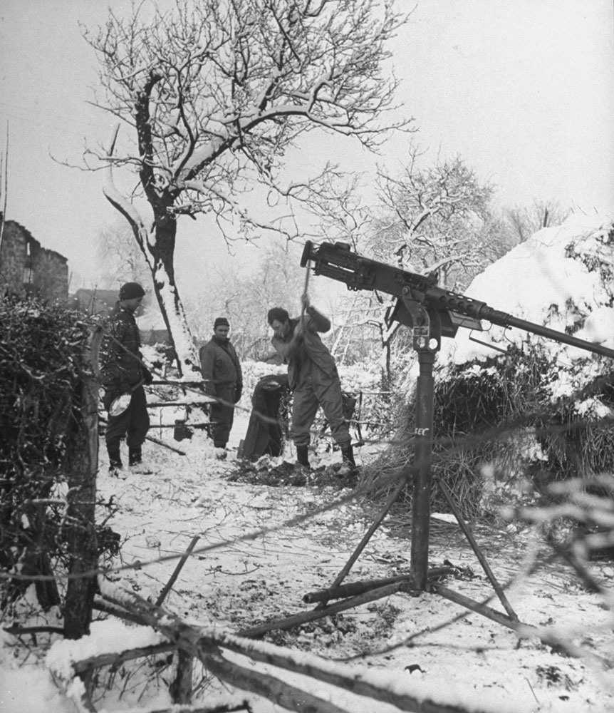 American GI's chop a foxhole in the frozen ground by a haystack during the Battle of the Bulge. The machine gun was set up in preparation for a German counterattack, expected at any moment.