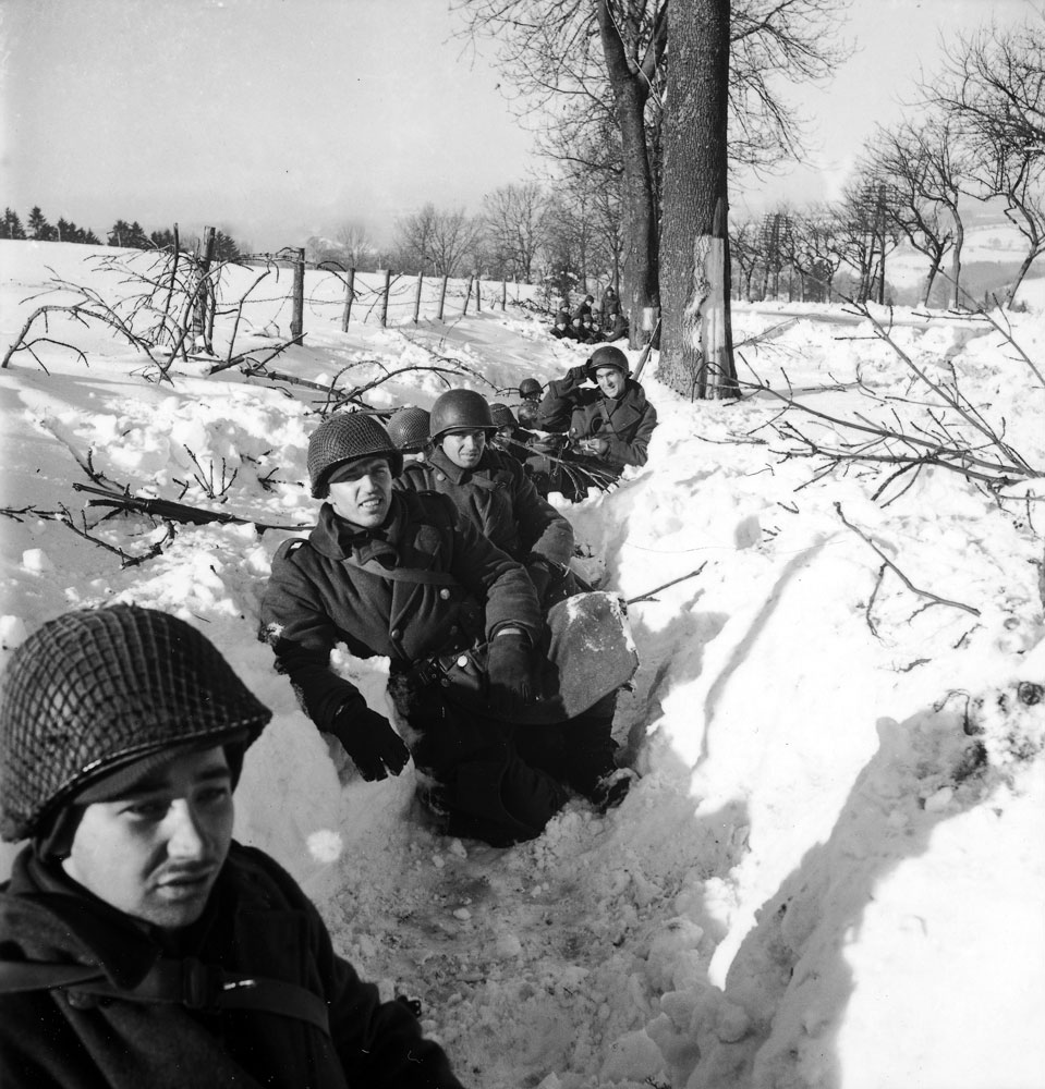 American troops in a snow-filled trench during the Battle of the Bulge.