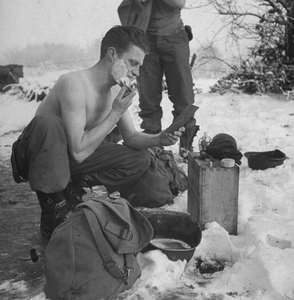 An American artilleryman shaves in frigid cold, using a helmet for a shaving bowl, during the Battle of the Bulge, 1944.