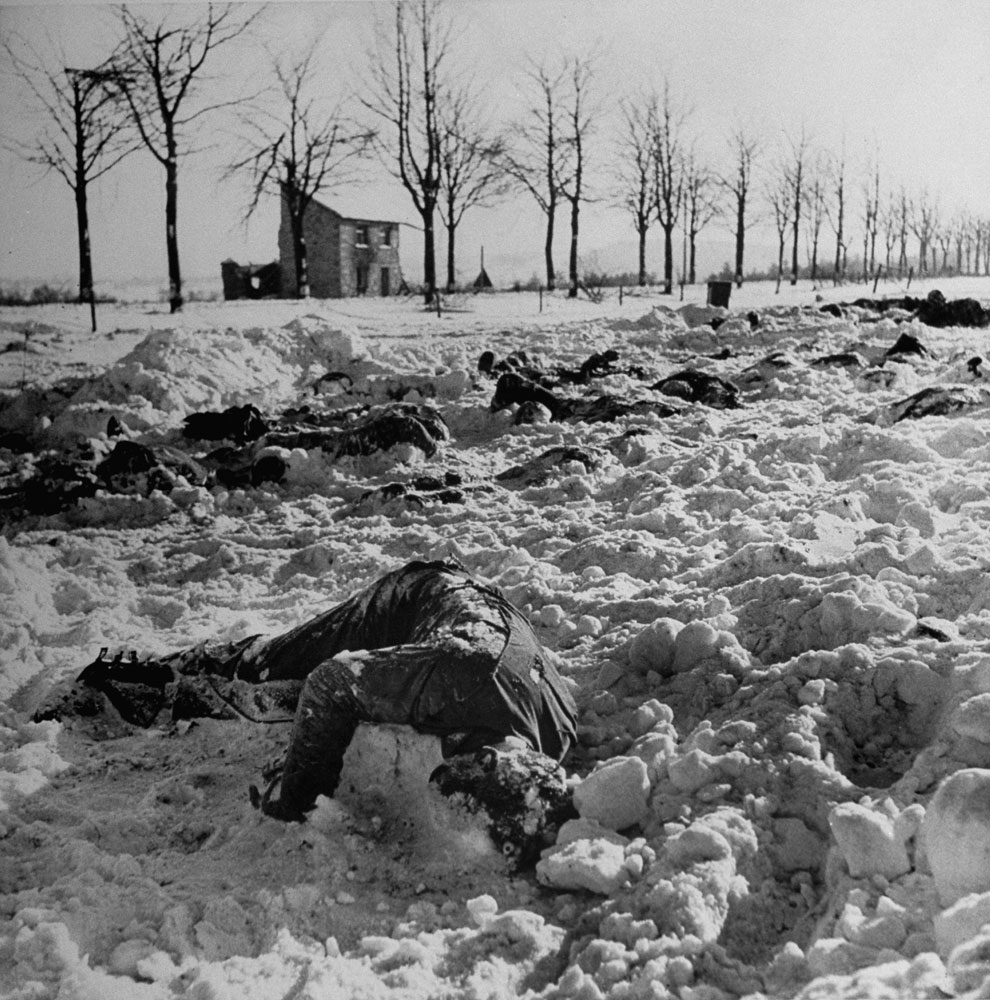 """Some of the 115 Americans who, LIFE reported, were """"massacred at point-blank range"""" in a field after being captured by Germans in the early days of the Battle of the Bulge, 1944. The soldiers were herded into a field and machine-gunned; when found, many of the frozen bodies still had their hands above their heads."""