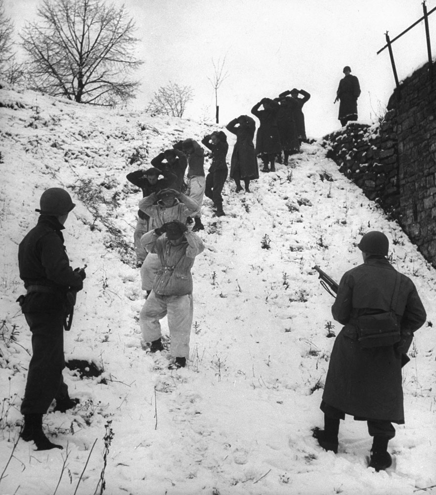 German prisoners, some of them wearing coveralls for camouflage in the snow, are herded by guards. (In close fighting, U.S. troops also used snow-camouflage suits.)