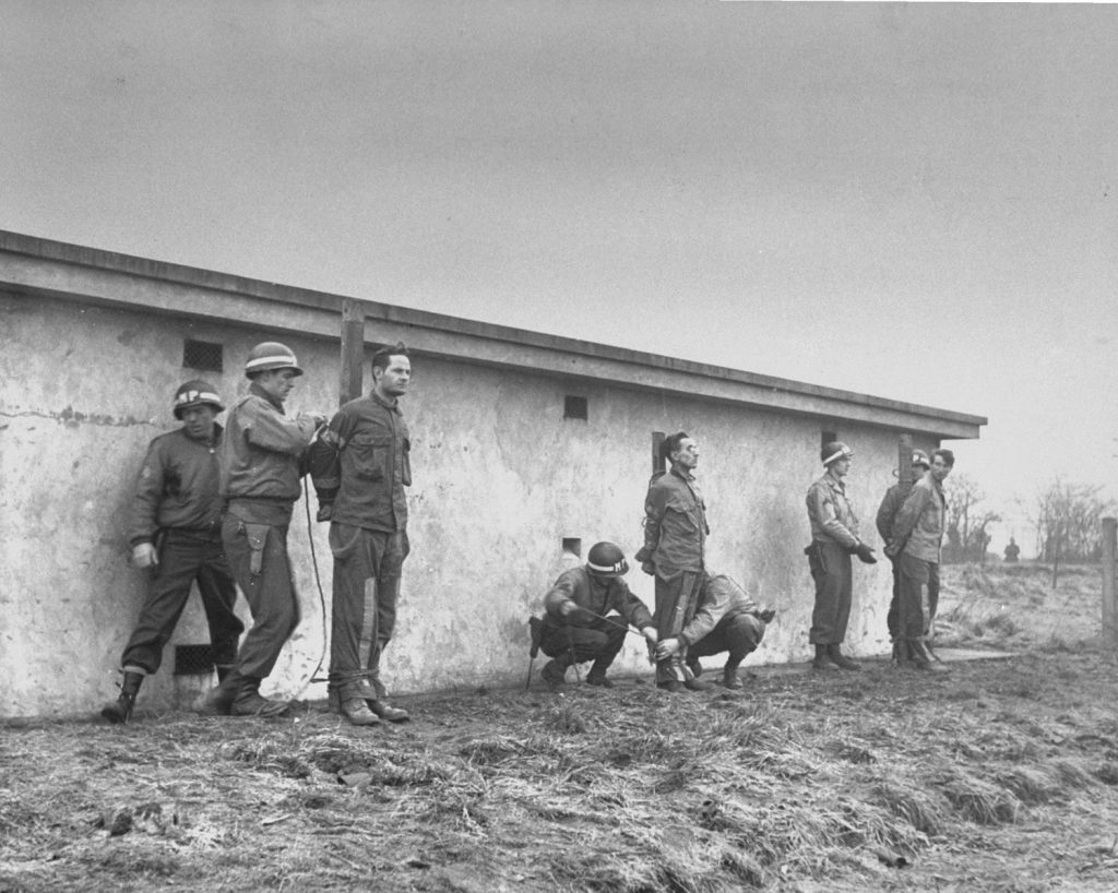 Photographed on Dec. 23, 1944, but not published in LIFE until June 1945. Behind a cell block, German prisoners are bound to stakes by MPs. Tried and convicted as spies, they are about to be executed.