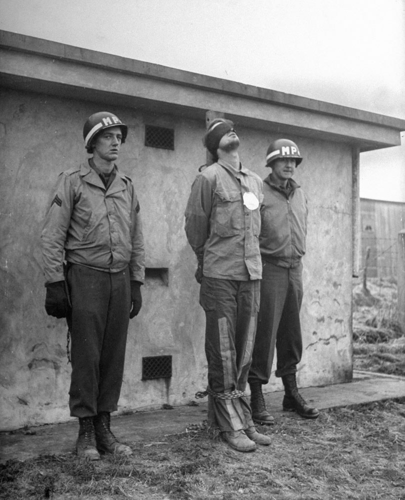 A blindfolded prisoner is securely bound, hand and foot, to a stake in front of a concrete wall. A large white paper target is pinned over his heart. American MPs stand at attention until the firing squad's commanding officer inspects the final arrangements. Belgium, 1944.