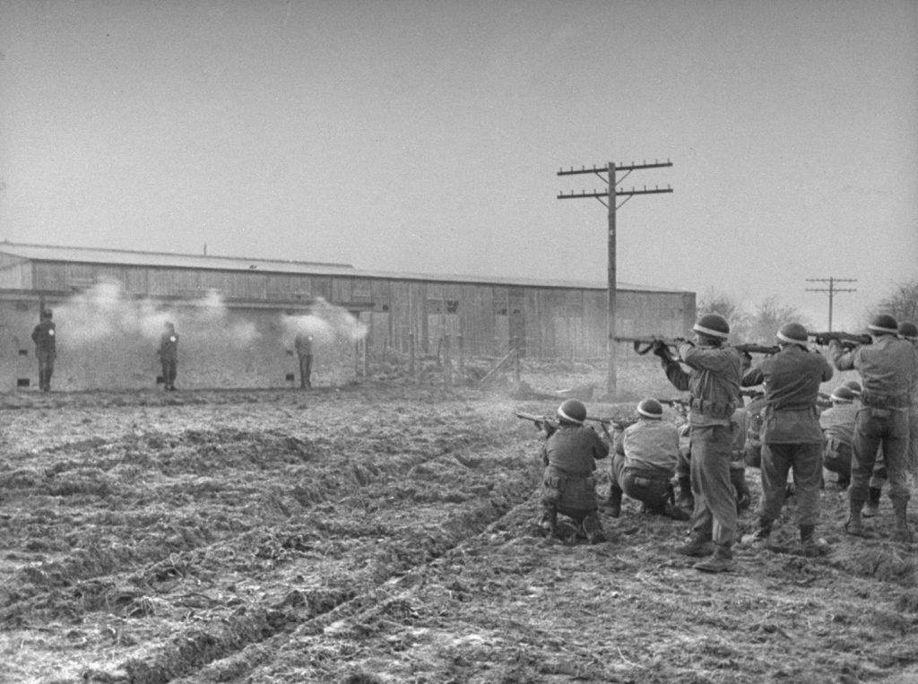 The volley is fired and three white puffs of smoke appear against the wall of the concrete block. The initial burst killed all three almost instantaneously. The firing squad, all military police, consisted of three groups of eight men, each with one additional marksman along as a spare.