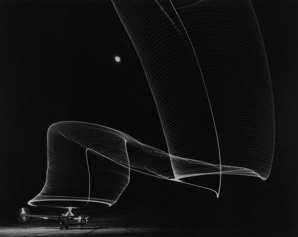Slinky-like light pattern produced by light-tipped rotor blades of a helicopter as it takes off into the dark sky, 1949.