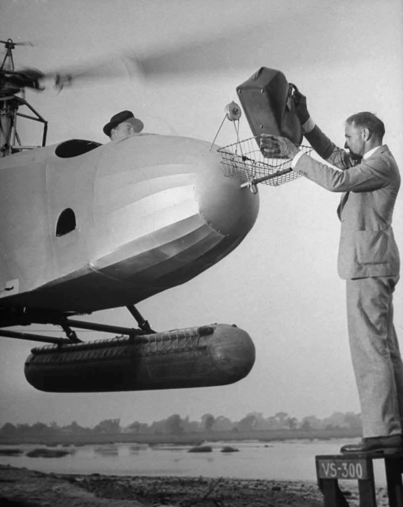 A man drops a briefcase into the basket on the nose of a helicopter, 1942.