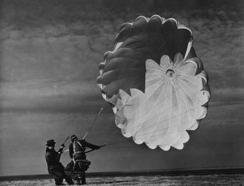 A parachute jumper testing equipment for the Irving Air Chute Co. gets some help while struggling to reel in his billowing chute, 1937.