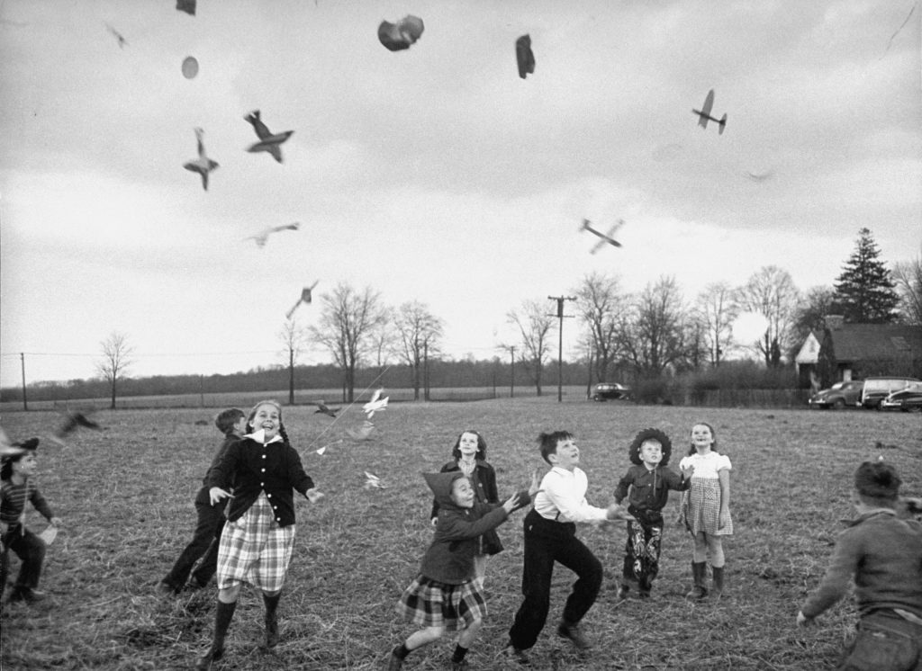 Children try to catch toys that were released by a kite, 1949.