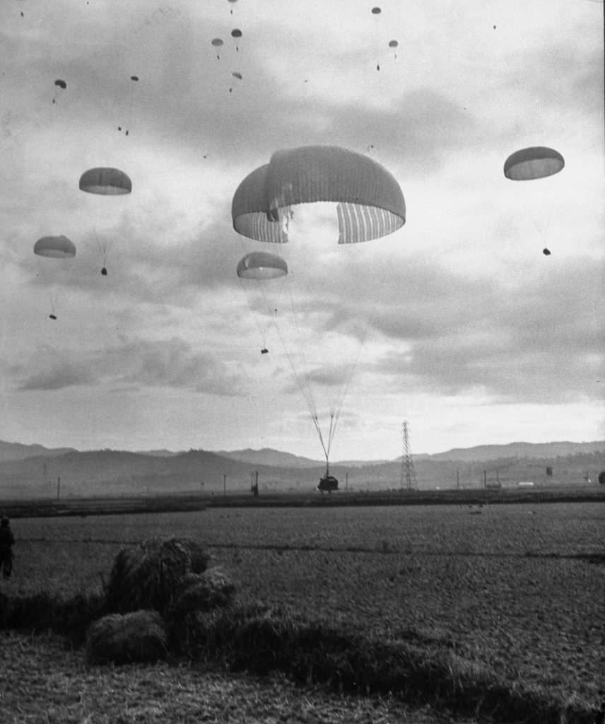 American paratroopers landing in Korea, with one ripped chute still holding enough air to drop safely, 1950.