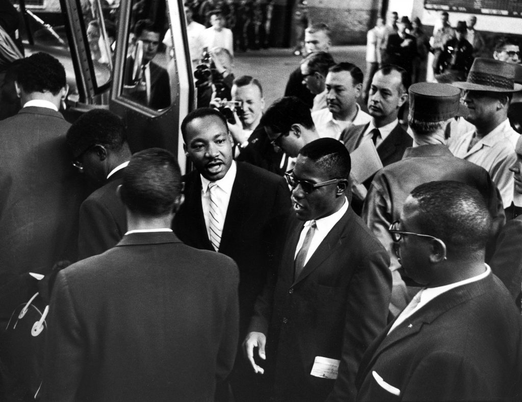 Martin Luther King Jr. encourages freedom riders as they board a bus for Jackson, Miss.