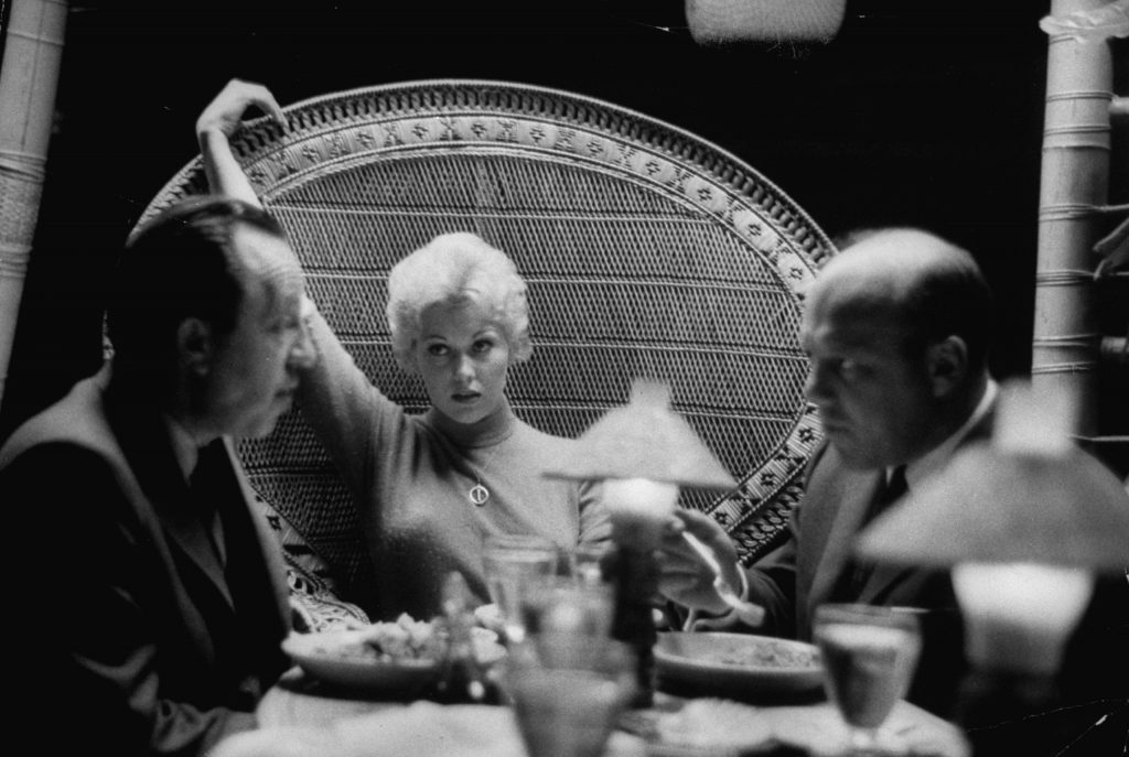 In a Beverly Hills Restaurant Kim Novak sits with a faraway look as agents Al and Wilt Melnick hotly discuss her blossoming movie career.