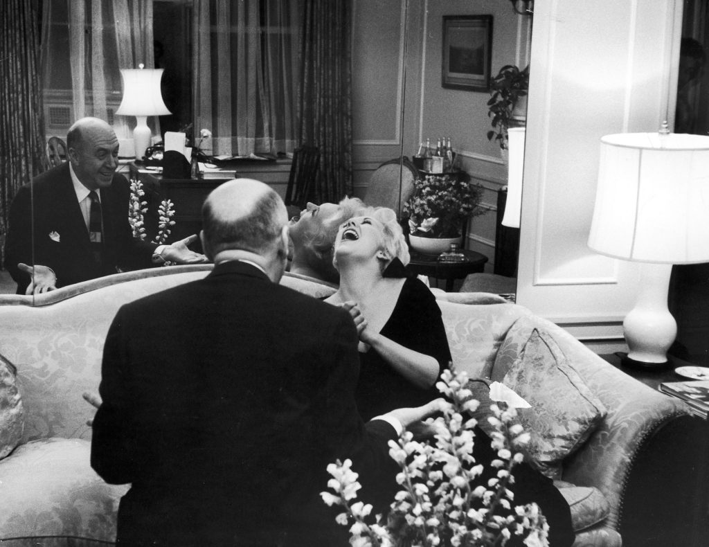 A rare laugh from somber Kim greets joke by Otto Preminger who visits Kim while she is in New York. She has great fondness and respect for Preminger, who directed her in United Artists' Man With the Golden Arm and put her genuinely at ease.