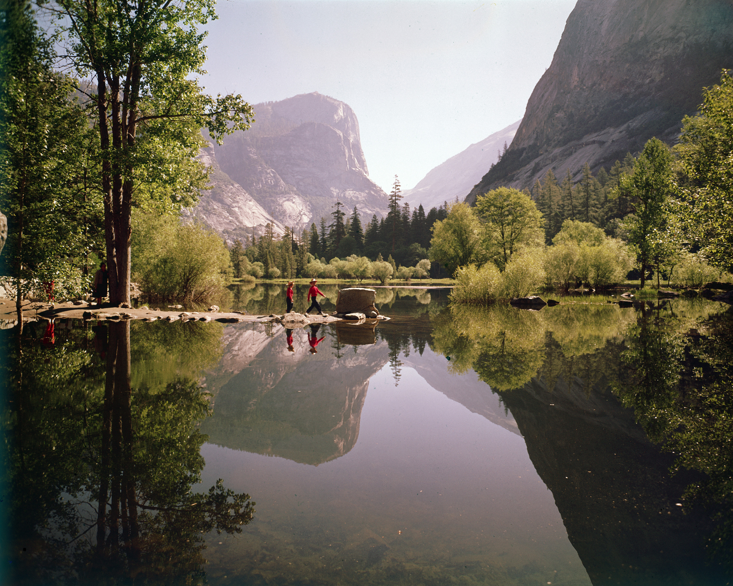 Children walk on a spit of rocks at Mirror Lake in Yosemite National Park, 1962.