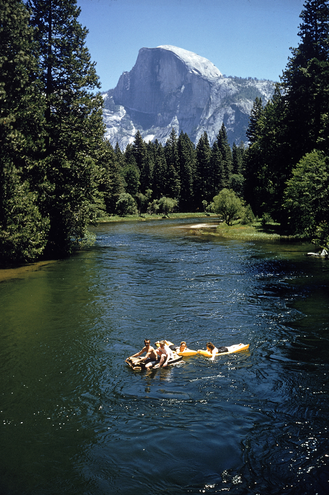 Tourists float on a raft in the Merced River, Yosemite National Park, 1962.