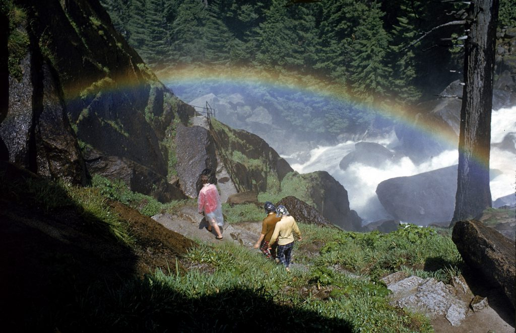 Hikers beneath a rainbow formed by mist from Vernal Falls, Yosemite National Park, 1962.